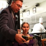 Our server, Mike, pours the champagne toast while Scarlett looks on