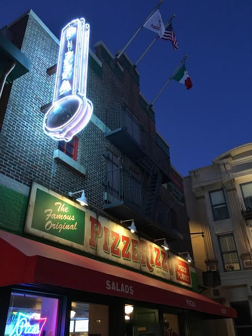Neon and classic pizzeria signs welcome you to PizzeRizzo.